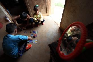 【流动娃】03孩子们几乎没有什么好玩的玩具,砖窑老板的儿子从县城带来的游戏纸牌成了他们的新鲜物,妹妹也跑来蹲在哥哥旁边观看。.JPG