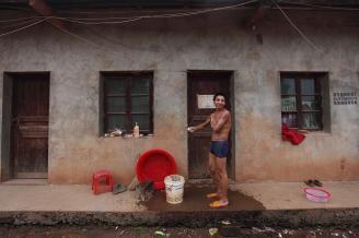【重庆窑工】05每天下工后,身上的灰尘和泥土特别多,下工后第一件事就是要洗澡。驻地没有浴室和澡堂,男工们就在自家门前洗澡,女工们就只能到公共厕所解决。.JPG